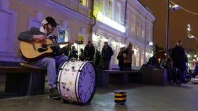 El hombre pone al músico del dinero que toca la guitarra en el centro de Moscú almacen de metraje de vídeo