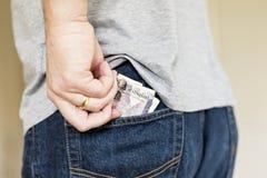 El hombre pone billetes de banco del efectivo en el bolsillo trasero de vaqueros Foto de archivo libre de regalías