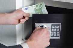 El hombre pone el dinero en la caja fuerte Fotos de archivo