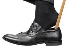 El hombre pone el zapato negro con el calzador aislado Foto de archivo