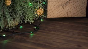 El hombre pone la caja de regalo debajo del árbol de navidad Soporte del abeto en la tabla de madera y adornado con la guirnalda  almacen de video