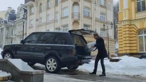 El hombre pone la maleta en el tronco del ` s del coche almacen de video