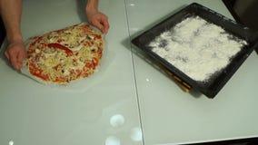 El hombre pone la pizza cruda en un molde para el horno Cocinar la pizza almacen de metraje de vídeo