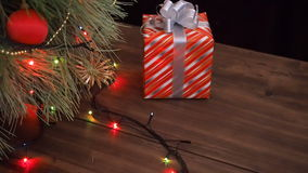 El hombre pone las cajas de regalo debajo del árbol de navidad Soporte del abeto en la tabla de madera y adornado con la guirnald metrajes