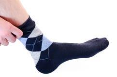 El hombre pone un calcetín Fotografía de archivo libre de regalías