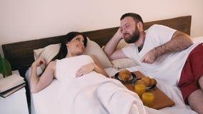 El hombre por la mañana en el dormitorio despertó su desayuno de la esposa en cama almacen de metraje de vídeo