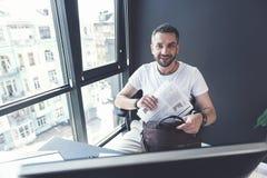 El hombre positivo adulto de moda está doblando documentos en su breve-bolso Fotografía de archivo libre de regalías