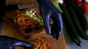 El hombre prepara el almuerzo, sirve el bocado asado a la parrilla del bocadillo del pan encima de tabla de cortar de madera, con metrajes