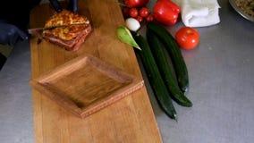 El hombre prepara el almuerzo, sirve el bocado asado a la parrilla del bocadillo del pan encima de tabla de cortar de madera, con almacen de metraje de vídeo