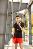 El hombre presenta al aire libre con una estafa de tenis y una bola Una toalla est? colgando en su hombro Concepto del deporte foto de archivo