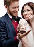 El hombre presenta la torta de cumpleaños a su novia que tenga gusto de ella Imagen de archivo