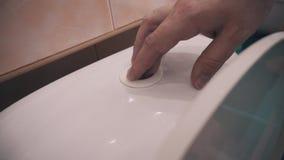 El hombre presiona el botón del dren del agua en el tanque del retrete Primer de la mano del hombre Sitio del retrete metrajes