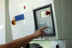 El hombre presiona el botón en panel de control electrónico Fotos de archivo libres de regalías