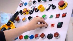 El hombre presiona los botones en el panel de control de producción metrajes
