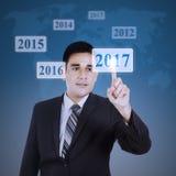 El hombre presiona los números 2017 en el botón virtual Fotografía de archivo