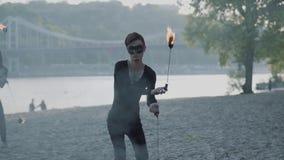 El hombre profesional en ropa negra y la mujer realizan una demostración con la llama mientras que se coloca en riverbank Firesho almacen de metraje de vídeo