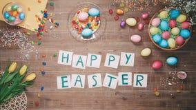 El hombre puso las palabras Pascua feliz en la tabla adornada con los huevos de Pascua Visión superior almacen de metraje de vídeo