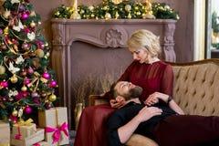 El hombre puso su cabeza en el sofá que se sentaba de la muchacha de las rodillas Imágenes de archivo libres de regalías