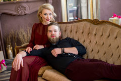 El hombre puso su cabeza en el sofá que se sentaba de la muchacha de las rodillas Foto de archivo libre de regalías