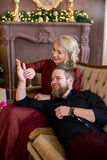 El hombre puso su cabeza en el sofá que se sentaba de la muchacha de las rodillas Foto de archivo