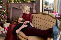 El hombre puso su cabeza en el sofá que se sentaba de la muchacha de las rodillas Imagenes de archivo