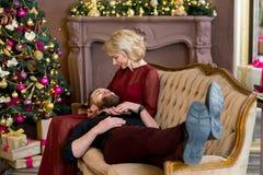 El hombre puso su cabeza en el sofá que se sentaba de la muchacha de las rodillas Imagen de archivo libre de regalías