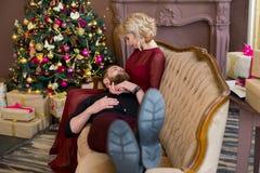 El hombre puso su cabeza en el sofá que se sentaba de la muchacha de las rodillas Fotografía de archivo libre de regalías