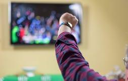 El hombre que aumenta la mano en el aire como equipo de fútbol gana en la TV imagenes de archivo
