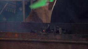 El hombre que aviva los carbones en la parrilla almacen de metraje de vídeo