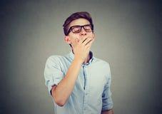 El hombre que bosteza con entrega su boca Imagenes de archivo