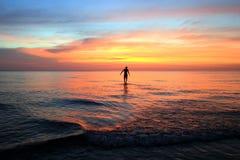 El hombre que camina en la playa en la puesta del sol colorida Foto de archivo