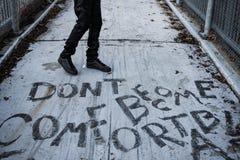 El hombre que camina a través de la acera con 'no hace cómodo 'escrito en él foto de archivo libre de regalías