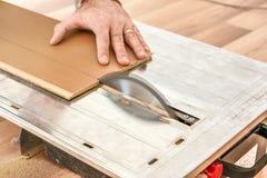 El hombre que cortaba los tableros de piso laminados en la circular vio, detalle en las manos que sostenían el panel de madera imágenes de archivo libres de regalías