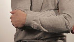 El hombre que da masajes al codo debido al dolor agudo en un fondo blanco