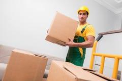 El hombre que entrega las cajas durante movimiento de la casa fotografía de archivo libre de regalías
