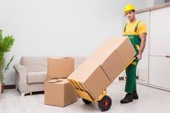 El hombre que entrega las cajas durante movimiento de la casa imagenes de archivo