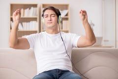 El hombre que escucha la música en casa Fotografía de archivo