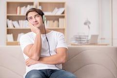 El hombre que escucha la música en casa Fotografía de archivo libre de regalías