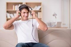 El hombre que escucha la música en casa Fotos de archivo