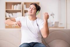El hombre que escucha la música en casa Fotos de archivo libres de regalías