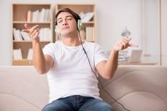 El hombre que escucha la música en casa Imágenes de archivo libres de regalías