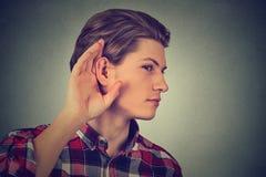 El hombre que escucha se sostiene con la mano al gesto del oído Imágenes de archivo libres de regalías