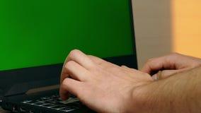 El hombre que espera con las manos en el teclado del ordenador portátil con greenscreen metrajes