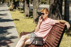 El hombre que habla por el teléfono en el banco en el parque fotos de archivo libres de regalías