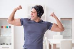 El hombre que hace deportes en casa y que escucha la música fotos de archivo libres de regalías