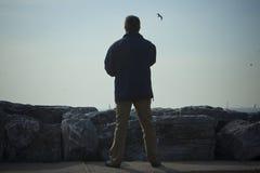 El hombre que hace el suyo estira en la playa Imagen de archivo