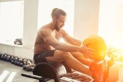 El hombre que el hacer se sienta sube con la bola de medicina en el banco, trabajando en los músculos abdominales Fotografía de archivo libre de regalías