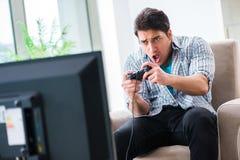 El hombre que juega al juego de ordenador en casa Imagen de archivo libre de regalías