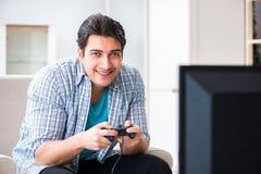 El hombre que juega al juego de ordenador en casa Fotos de archivo