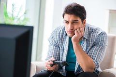 El hombre que juega al juego de ordenador en casa Imágenes de archivo libres de regalías